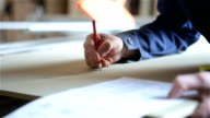 The worker makes notes on the wooden workpiece. video