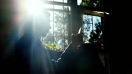 The young businessman in an abandoned house. He sits on the windowsill, uses a telephone. Silhouette in the sun video