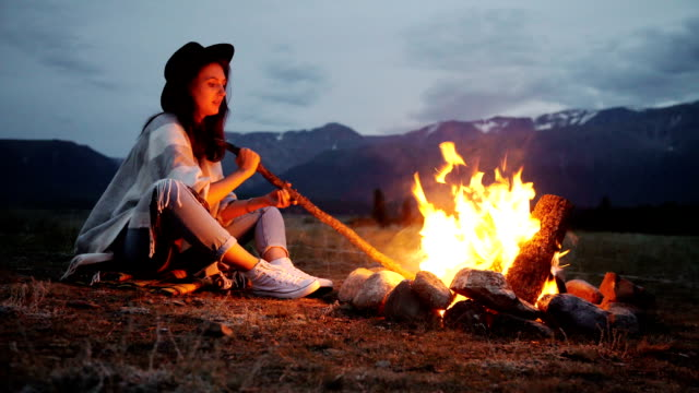 The young girl and men drink tea coffee and rest by bonfire background. video