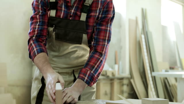 4K The young joiner master measures wooden bars in the woodworking industry. video