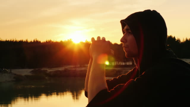 The young man dreams at sunset. He's in the hood: sitting profile to the camera video
