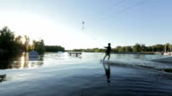 The young man fast rides on a wakeboard against the sunset in the wake park video