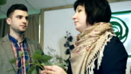 The young man is learning from a professional florist haw to work with flowers. video