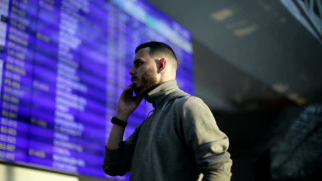 The young man is tapping number on mobile phone standing next to the information board at the airport. video