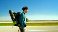 The young man with the big backpack, hipster, tourist and hitchhiker, walking along the highway in Illinois, USA. video