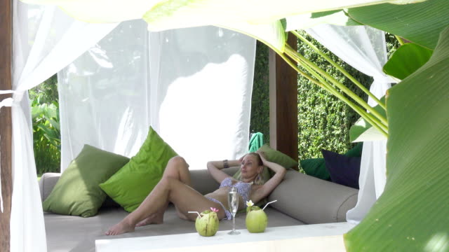 The young slender woman in bikini with a long fair hair has a rest in the tropical resort video