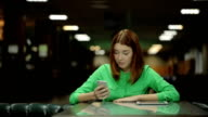 The young woman is sitting at the table and cafe working with the cell phone waiting for the order video