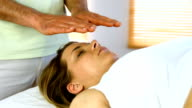 Therapist performing reiki on patient video