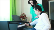 Therapy for young man in wheelchair using piano video