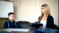 Therapy session classroom with boy listening the woman psychologist speech video