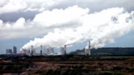 Thermal power station at open-cast coal mine under blue sky, smoking chimneys at background. video