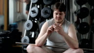 Thick serious young man in the gym uses his smartphone video