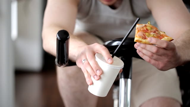 Thick tired man with piece of pizza in his hand spinning exercise bike pedals and drinking soda video