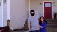 A thief wearing a ski masks stands in front of a house with arm around a woman video