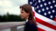 Thinking teenage girl with American flag behind her video