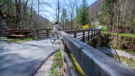 This couple cycling through the beautiful small bridge on a countryside, because they are enjoy watching nature. video