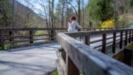 This two young cycler s cycling through the beautiful small bridge on a countryside, because they are looking this beautiful nature. video