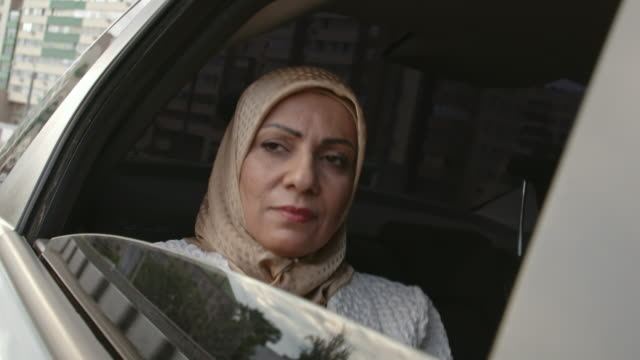 Thoughtful Arab woman riding in back seat video