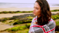 Thoughtful brunette wrapped in a blanket sitting by the beach video
