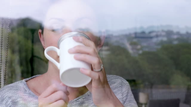 Thoughtful woman enjoying a coffee video