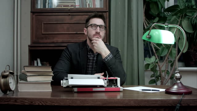 Thoughtful writer sitting in front of typewriter waiting for inspiration for his new book video