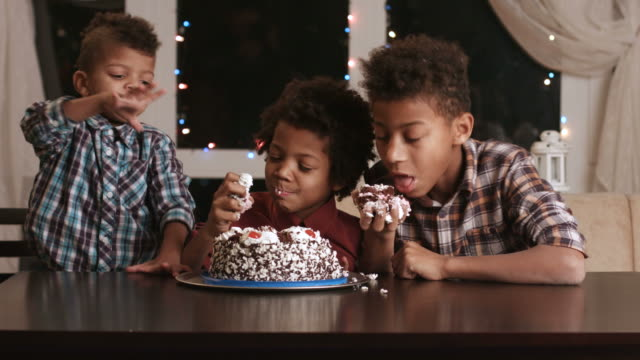 Three afro boys eating cake. video