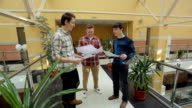 Three architects happily discuss development of working project video