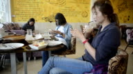Three Asia people texting, sending sms on smartphone in cafe video