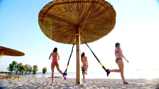 three athletic, sexy young women in swimsuits, instructors, doing exercises with fitness trx system, TRX suspension straps. On the beach, in summer, at sunset, in sun rays video