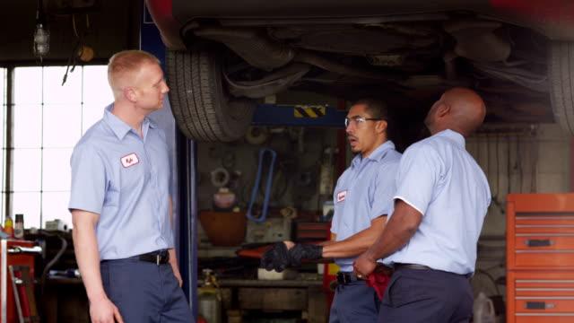 Three auto mechanics look at car together video