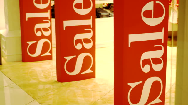 Three big red sales signs on shop entrance magnetic gates. Promotion. Consumerism concept video