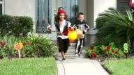 Three boys in halloween costumes, trick or treating video