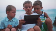 Three boys sitting on the rocky shore. video