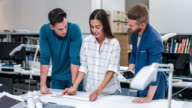 Three business colleagues working with blueprints at office video