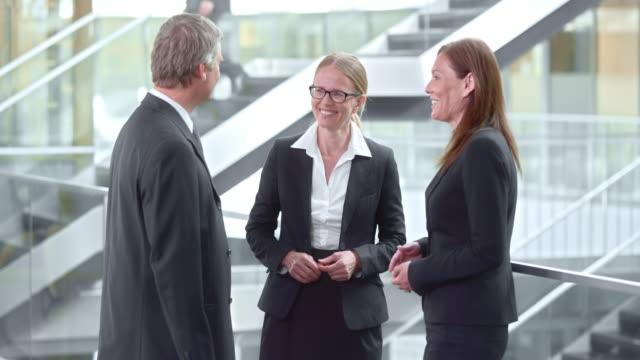 TU Three business people talking in the hallway video