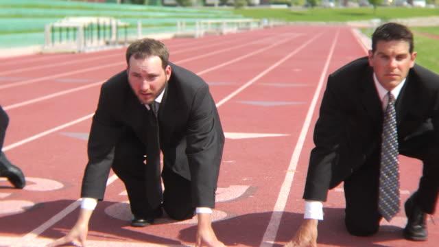 Three businessmen at starting line video