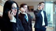 Three businessmen speak by phone in the hall video