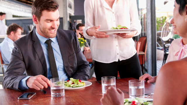 Three Businesspeople Having Working Lunch In Restaurant video