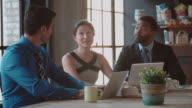 Three Businesspeople Working At Laptops In Café Shot On R3D video