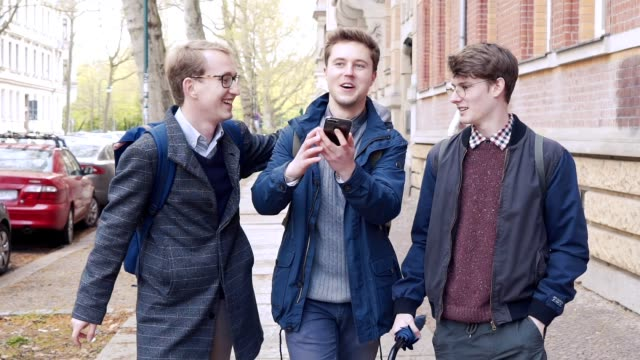 Three cheerful friends joke and sing while walking along the city street video