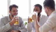 Three cheerful men in casual wear toasting video