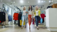 Three cheerful young women are walking through a department store in colorful garments. video