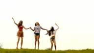 Three cheerful young women holding hands and jumping,slow motion video