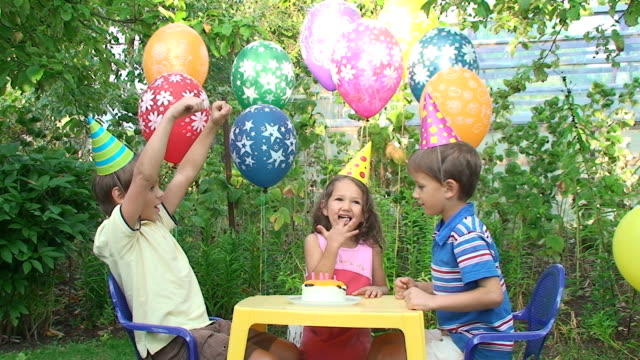 Three child at a birthday party in the garden video