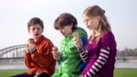 Three children 8-10 years, receive and start eating ice cream video