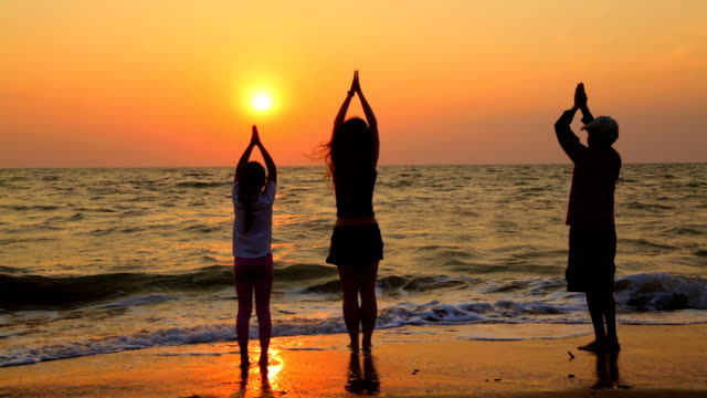 Three Children Doing Yoga Exercises On The Beach At Sunset video