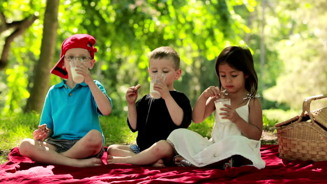 Three children have fun eating cookies and milk. video