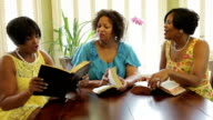 Three Christian women join hands in prayer after Bible study video