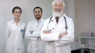 Three clinicians in white coats looking and smiling at camera video