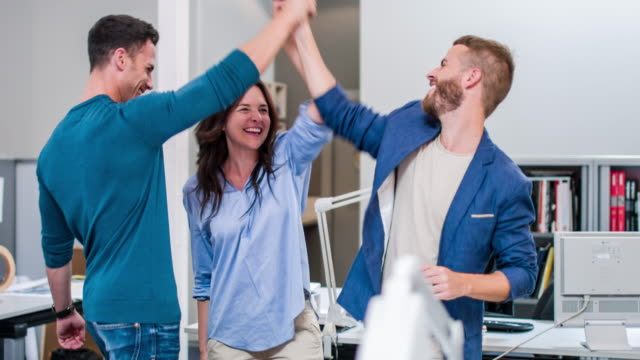 Three creative business colleagues giving high-five video